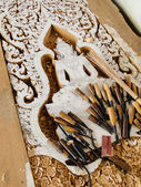 Wood carvings with religious design. carving tools are lying on — Stock Photo