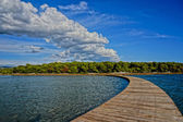 Wooden walkway leading into the horizon. clouds mirroring the s — Stock Photo