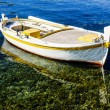 Stock Photo: Small rowing boat is anchoring in clear water.