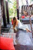 Attractive women sitting on a swing — ストック写真