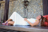 Attractive woman is reclining on a swing or a bench — Stok fotoğraf