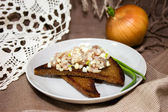 Appetizer of herring with chopped eggs and onions with fried bread. — Stock Photo