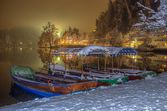 Pletna boats moored on the bank of Lake Bled in Winter snowy night — Stock Photo