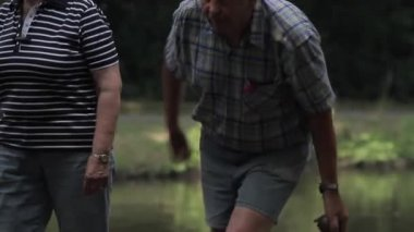Elderly people enjoying boule in a park, ball shooting — Stockvideo