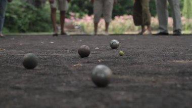 Elderly people enjoying boule in a park, ball shooting — Stock Video