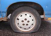 Flat tire on rusty blue van parked on asphalt — Stock Photo