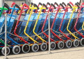 A line of colorful shopping carts in daylight — Stock Photo