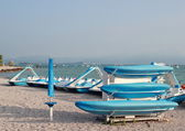 Blue boats and water cycles at rubble beach in the morning — Stock Photo