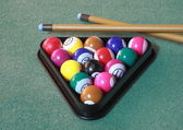 Pool balls on green cloth in triangle with cues — Stock Photo