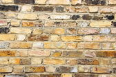Old worn urban brick wall with different tiles — Stock Photo
