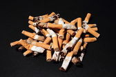 Pile of used cigarette butts on black background — Stock Photo