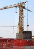 Construction crane with heavy contrablocks and blue sky — Stock Photo