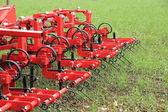 Harrow in green crop field after rainfall — Stock Photo