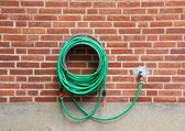 Green water hose hanging red brick wall — Stock Photo