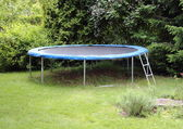 Blue trampoline on the lawn in garden — Stock Photo