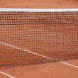 Tennis net at empty red gravel court — Stock Photo #47751439