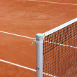 Tennis net at empty red gravel court — Stock Photo #47751461