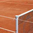 Tennis net at empty red gravel court — Stock Photo #47751477