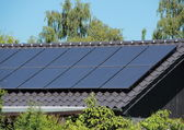 Solar collector on house roof with blue sky — Stock Photo