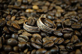Two gold wedding rings in coffee beans. — Stok fotoğraf