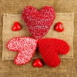 Knitting hearts on the sackcloth — Stock Photo