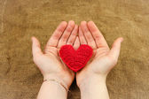 Knitting heart in the hands — Stock Photo