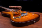 Glass of rum and cigars on the electric guitar — Stock Photo