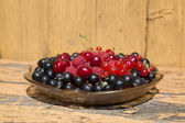 Cherry currants raspberries in a glass dish on a wooden table — Stock Photo