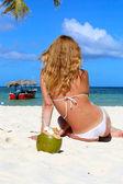 Girl in a white bikini sits near the coconut on a white sand bea — Stock Photo