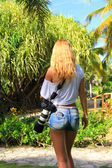 Girl with the camera on a Sunny day among palm trees — Stock Photo