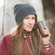 Young woman holding cup of hot drink outdoor — Stock Photo #39547513