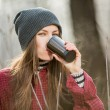 Young woman holding cup of hot drink outdoor — Stock Photo #39547515