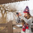 Smiling young woman taking photo in winter park — Stock Photo #39558801