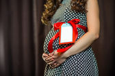Pregnant woman touching her belly with hands — Stock Photo