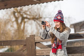 Smiling young woman taking photo in winter park — Stock Photo