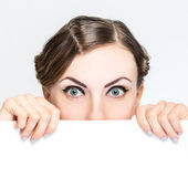 Woman peeking out from behind billboard paper poster — Stock Photo