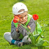 Smiling boy with spring flowers — Stok fotoğraf