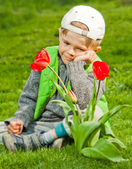 Smiling boy with spring flowers — Foto Stock