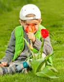 Smiling boy with spring flowers — Photo