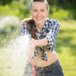 Gardener woman watering — Stock Photo