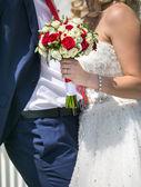 Sposi con fiori rossi brillante — Foto Stock