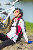 Beautiful sport smiling girl sitting next to bike — Stock Photo