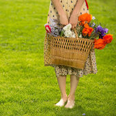 Woman with basket flowers — Stock Photo