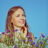 Beautiful young woman among flowers and blue sky — Stock Photo