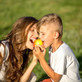 Happy family eating apple — Stock Photo
