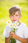 Cute little boy with flowers — Stock Photo