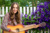 Woman playing guitar in park — Stock Photo