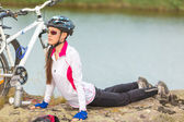Cute female cyclist relaxing after riding a bike — Stock Photo