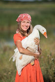 Woman farmer holds goose happy smiling — Stock Photo