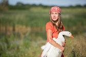 Young woman care about animal goose — Stock Photo